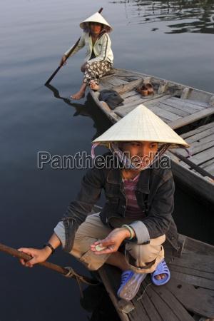 women ferrying boats await a fare
