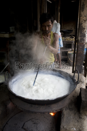 street yogurt maker stirring milk india