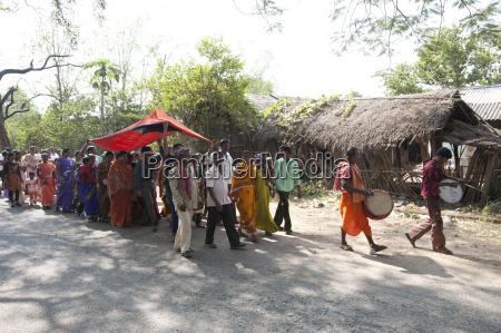 drummers leading village bride under red