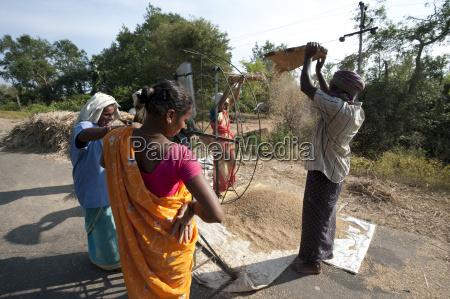 women turning portable fan to assist