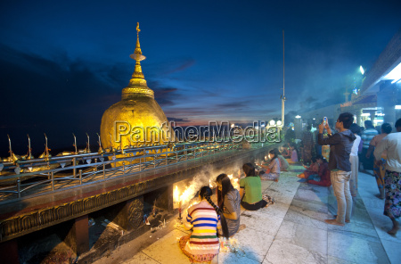 buddhist pilgrims lighting candles and visitors