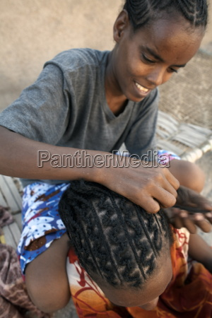 girls plait their hair in traditional