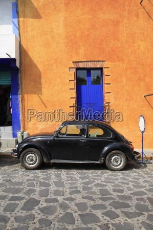 volkswagon beetle parked on cobblestone street