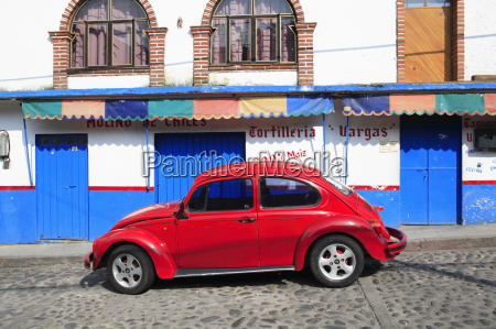 red volkswagon beetle parked on cobblestone