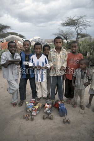 children with home made toys pose