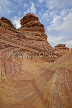 sandstone wave and cones under clouds