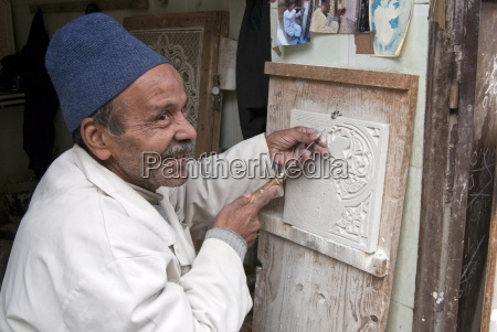 craftsman at work on stucco carving