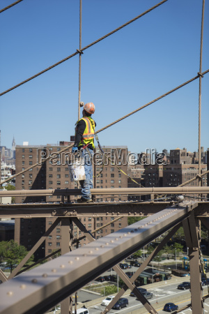 workman repainting beams and cables on