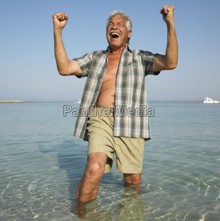 happy senior man on beach with