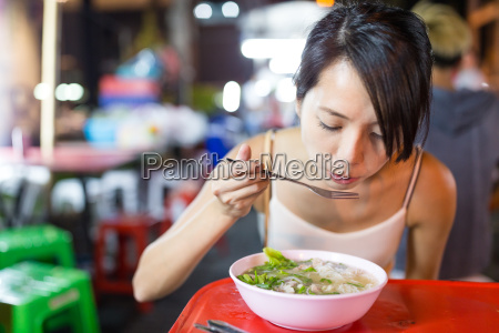 woman eating in night market of