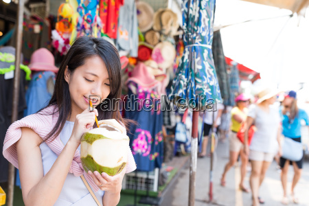 woman drinking of coconut at street