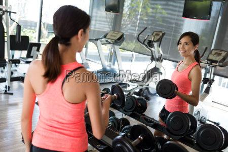 woman training on dumbbell inside gym