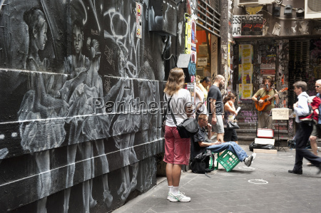 graffiti and people watching street musician