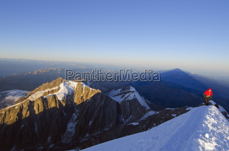 climber on summit of mont blanc