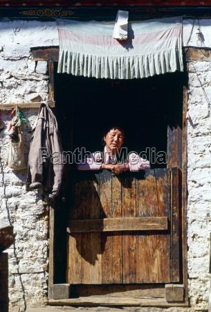 woman at doorway of house paro