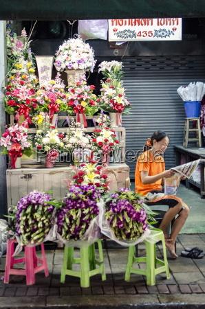a flower seller reads the morning