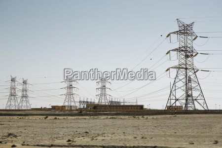 electricity pylons dominate the flat barren