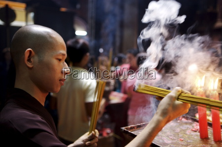 monk lighting joss sticks during ceremony
