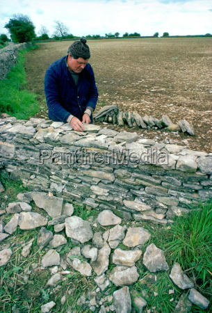 man building a dry stone wall