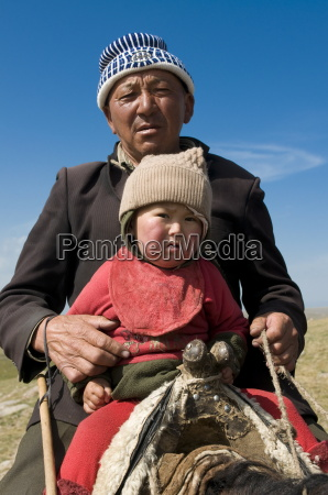 grandfather with his grandson riding a