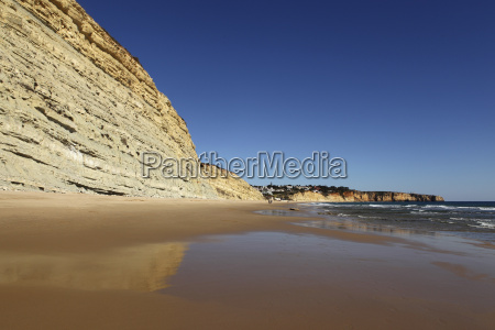 golden sands and steep stratified cliffs