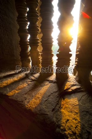 sunset through stone pillars at angkor