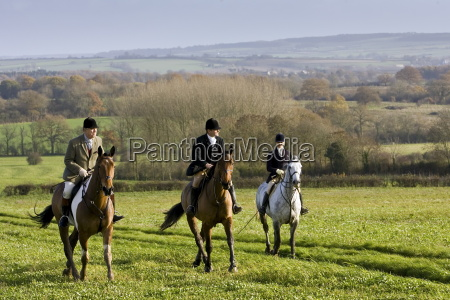 members of heythrop hunt ride across