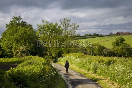women walks down a country lane