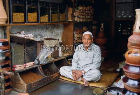 shopkeeper sitting cross legged in his