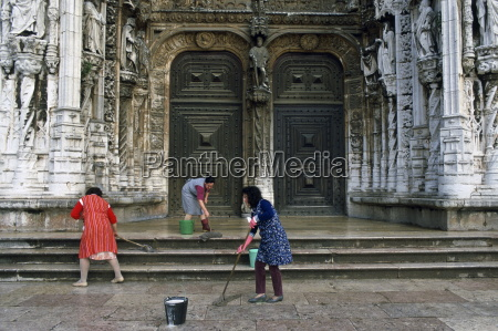women cleaning the steps outside a