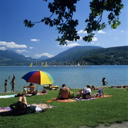sunbathers along shore of lake annecy