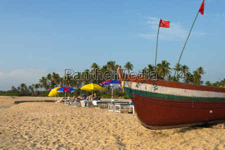 traditional fishing boat and sunbathers on