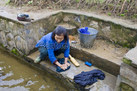 woman washes her clothes in a