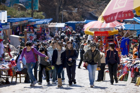 tourists walk through souvenir stalls at