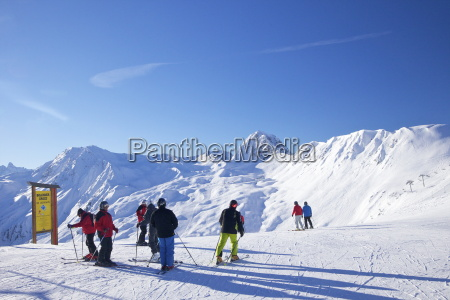 skiers on piste early morning in