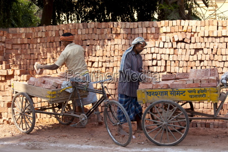 indian men stacking tata bricks in
