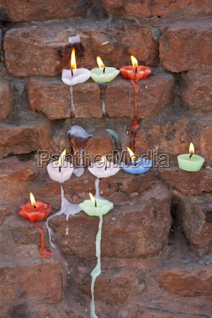 lighted candles offering buddhist prayers at