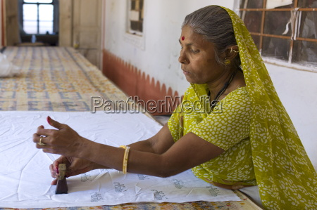 indian woman die stamping textiles at