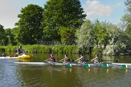 coach trains oarsmen rowing skiff on