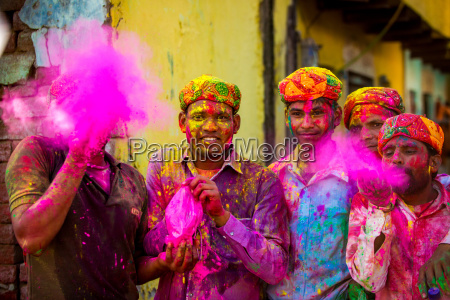 men throwing colored pigment holi festival