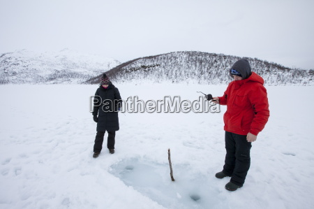 couple ice fishing on frozen lake
