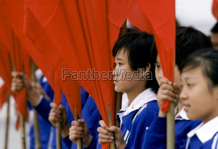 young chinese students with red flags