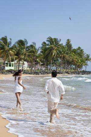 hispanic couple running along the shore