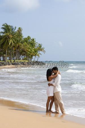 hispanic couple embracing on lapared beach