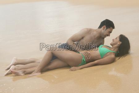 hispanic romantic couple lying on the