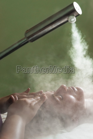 woman receiving a steam facial spa