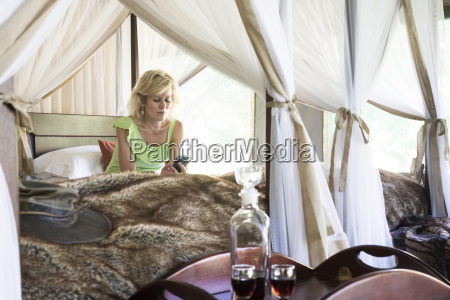 woman texting from canopied bed in