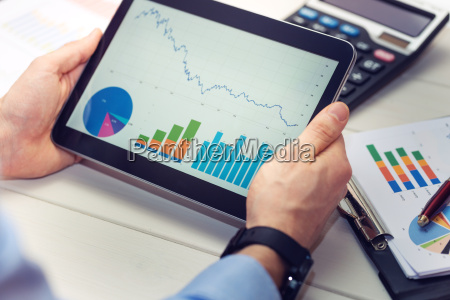 businessman holding digital tablet with graphs