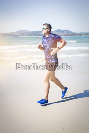 athletic man running on the beach