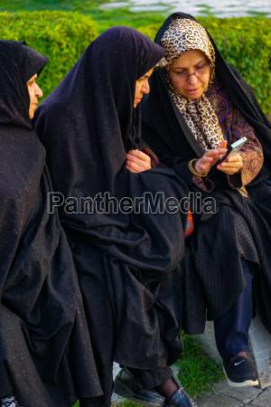 three old iranian women transfixed by